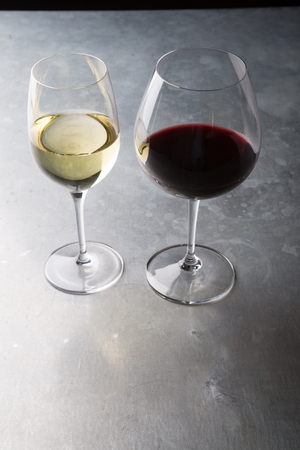 Red and white glasses of wine on a ber counter Stock Photo