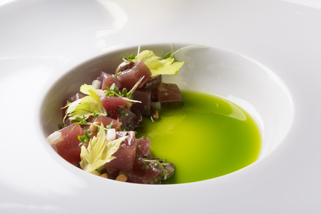 Fresh tartar served on a white plate with green sauce