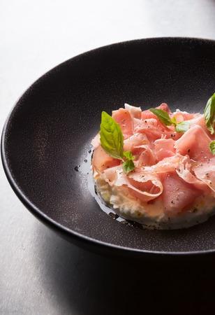 Prosciutto ham served on a black plate