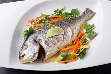 Whole steamed dorado fish served with salad