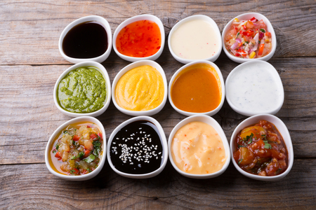 Different type of sauces served on wooden board