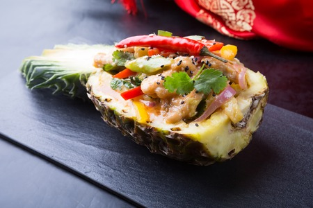 Pineapple, stuffed with rice and spicy chicken