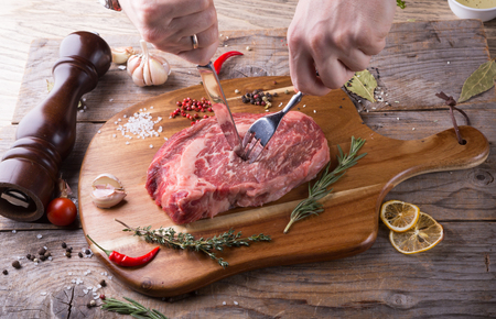 Hand cutting raw beef steak