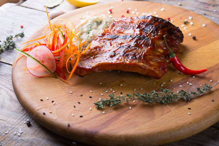 Fried ribs served with mashed potatoes on wooden board Archivio Fotografico