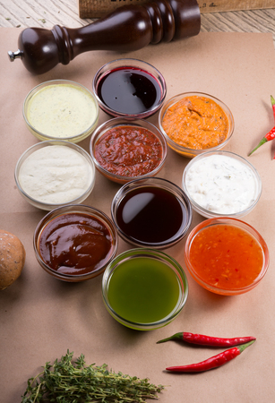 Different types of sauces background. Set of sauces - ketchup, mayonnaise, mustard, soy sauce, bbq sauce, pesto, mustard grains and pomegranate sauce Reklamní fotografie - 104930639
