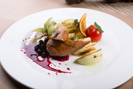 Roasted and sliced duck meat served with apple