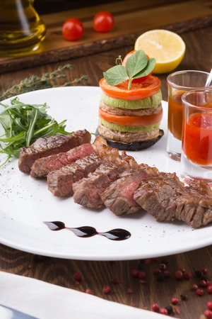 Juicy freshly grilled steak served with chili sauce and vegetables