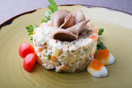 Russian olivier salad served with ham and red caviar Stock Photo