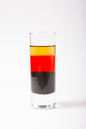 Strong alcohol glass shot coloured in german flag