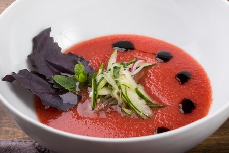 Spanish tomato gazpacho soup served with basil leaf Archivio Fotografico