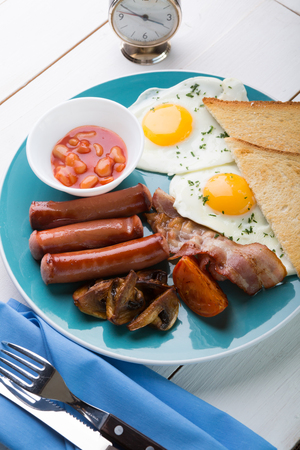 Full english breakfast with fried eggs, bacon, beans and sausage.