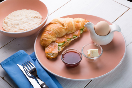 Oatmeal porridge served with croissant and boiled egg