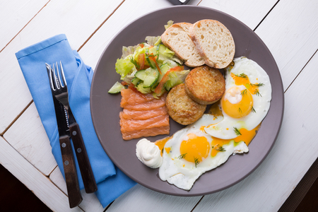 Breakfast if two fried eggs with salmon, hash browns and salad