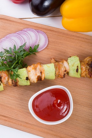 Grilled meat with zucchini on a skewer served on a wooden board