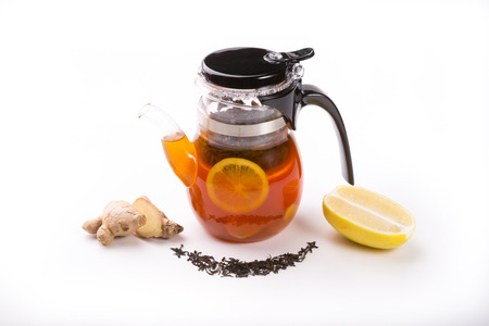 Glass teapot on white background with fresh brew of tea