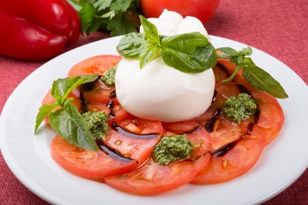 신선한 생 토마토와 바질 잎을 곁들인 버팔로 부라타 치즈