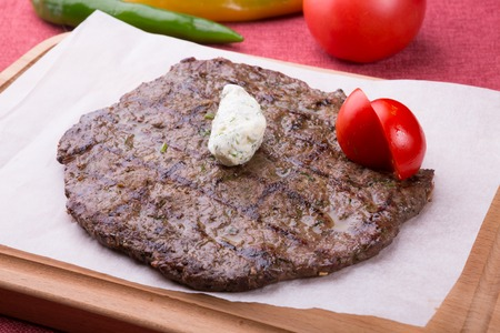 Fried horse meat steak with butter served on wooden board