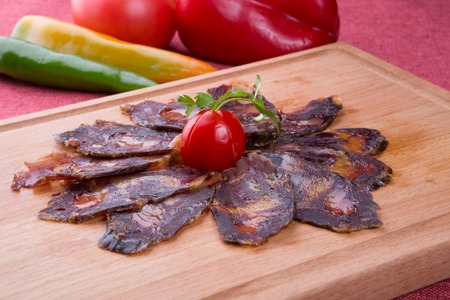 Rustic raw smoked meat sliced and served on wooden board