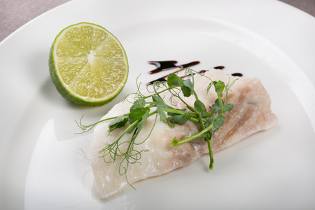White fish fillet served with lime and sauce