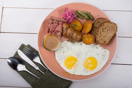 Fried egg served with pastrami and baked potatoes