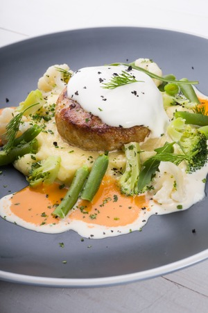Beef cutlet served with mashed potatoes, broccoli and cauliflower in a grey plate