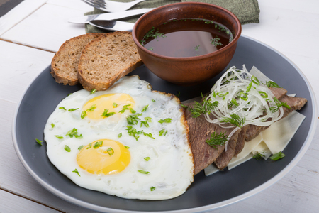 Fried eggs served with bread slices, meat slices and broth for breakfast Reklamní fotografie