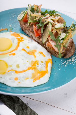 Fried eggs served for breakfast with pate sandwich