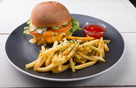 Burger served with french fries and ketchup on a plate