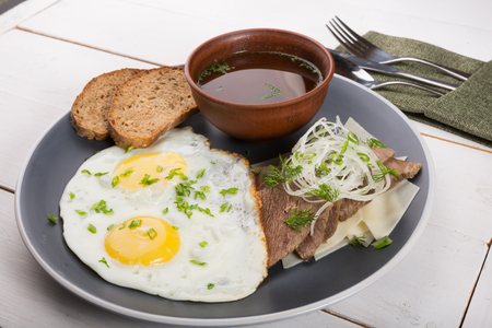Fried eggs served with bread slices, meat slices and broth for breakfast Standard-Bild