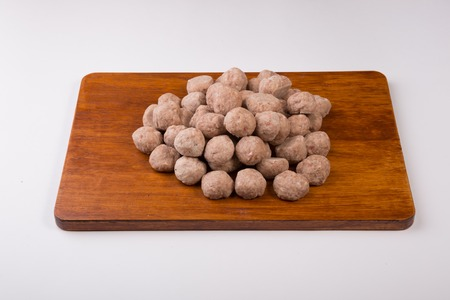 Raw fresh uncooked meatballs on a wooden chopping board