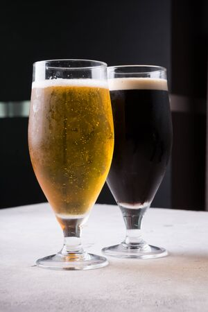 Two full glasses light and dark of cold beer