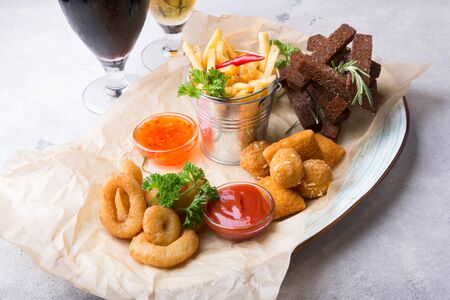 Different beer snacks served with sauces and two beer glasses 스톡 콘텐츠