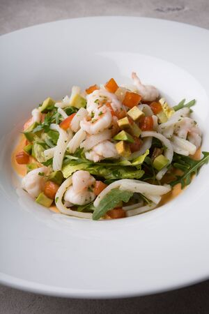 Freshly cooked seafood salad served on a white plate Фото со стока