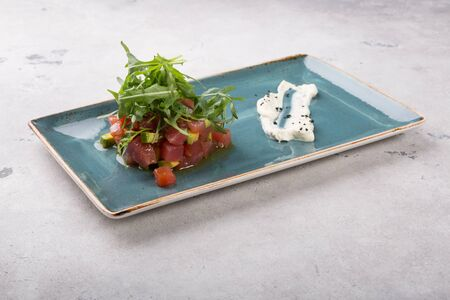 Raw fresh delicious tartare dish served with avocado and arugula 스톡 콘텐츠