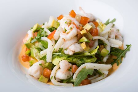 Freshly cooked seafood salad served on a white plate 스톡 콘텐츠