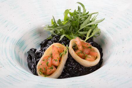 Black seafood risotto served with arugula on a white plate Фото со стока