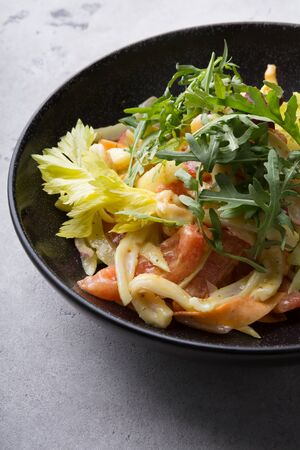 Fresh green squid salad with arugula served in a black ceramic bowl