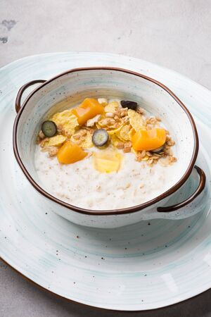 Fresh cooked oatmeal porridge served with grapes, cereal and fruits