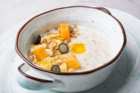 Fresh cooked oatmeal porridge served with grapes, cereal and fruits Banque d'images