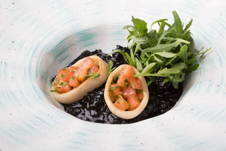 Black seafood risotto served with arugula on a white plate 스톡 콘텐츠