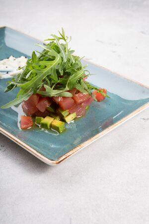 Raw fresh delicious tartare dish served with avocado and arugula Фото со стока