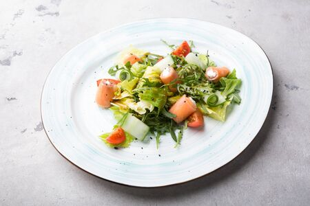 Salmon and white cheese mixed vegetable salad served with arugula Stock Photo