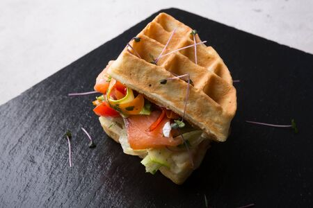 Belgian waffles sandwich with smoked salmon and vegetables