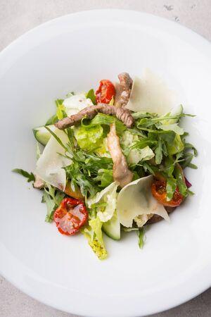 Fresh healthy roastbeef salad with green arugula and parmesan cheese