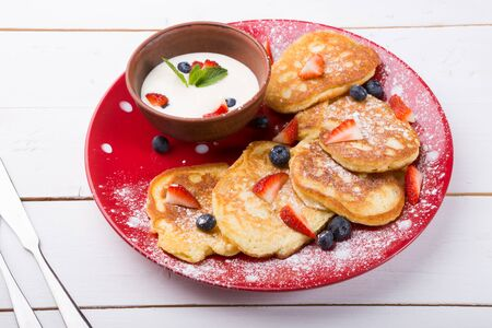Pancakes served with strawberries and blueberries on a red plate 写真素材
