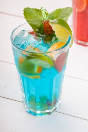 Glass of blue alcohol cocktail decorated with mint leaf