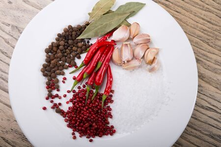 Different sorts of spices and herbs on a white plate 写真素材