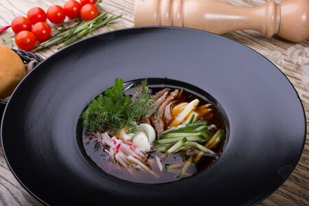 Traditional russian summer cold soup okroshka in a black bowl