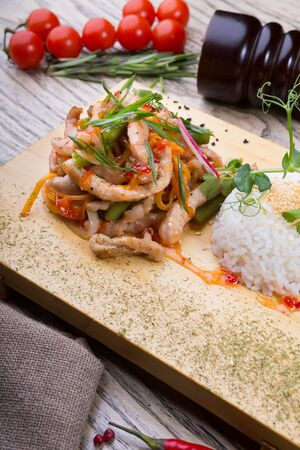 Chinese chicken with rice garnish served on a wooden board