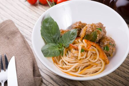 Bowl of spaghetti with meatballs and basil